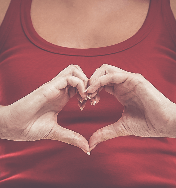 A woman making a love heart with her hands.