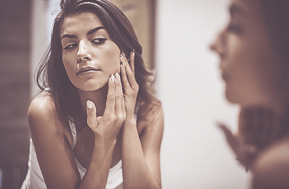 A woman checking her face in the mirror.