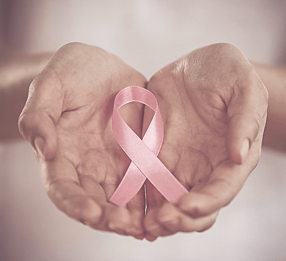 A pink cancer ribbon in a woman's hands.