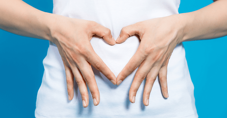 An image of a woman making a heart with her hands over her stomach.